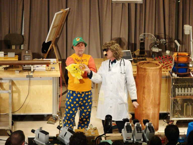 Professors on stage conducting an experiment