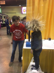 woman helping kid on van de graff generator