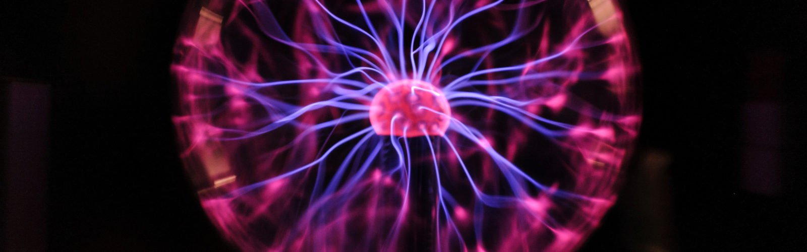The conduction of electrons radiates from a Tesla coil within a plasma ball during a Wonders of Physics show