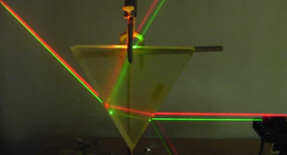 A red and a green laser refracting through a prism