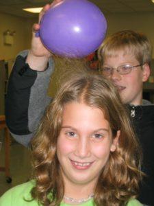 Boy Holding balloon above girl's head