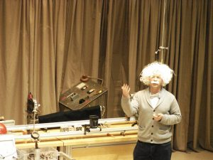 a man dressed similarly to Einstein is about to perform a demo